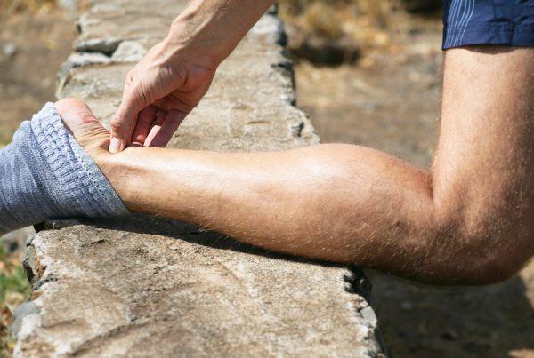 Achilles tendinitis man holding ankle